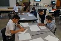 In art, Fr. Ignatius works with the Form IV boys in creating patterns with geometric shapes after studying examples.
