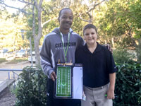 Coach Dotson and the winner of the 7th Grade Design-a-Play auctioned at Homecoming.